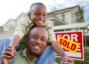 Man with son on his shoulders in front of a sold sign for a house